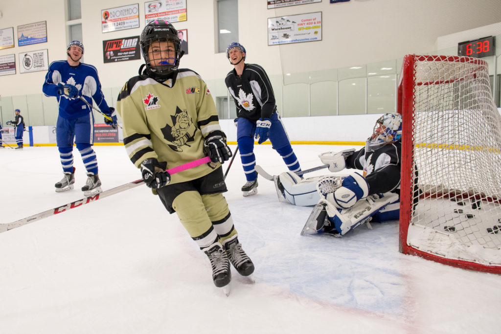 A young hockey player shoots on Marlies goalie Garret Sparks at a community festival