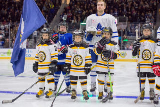 Minor hockey players stand with the Marlies as part of the Future Stars experience