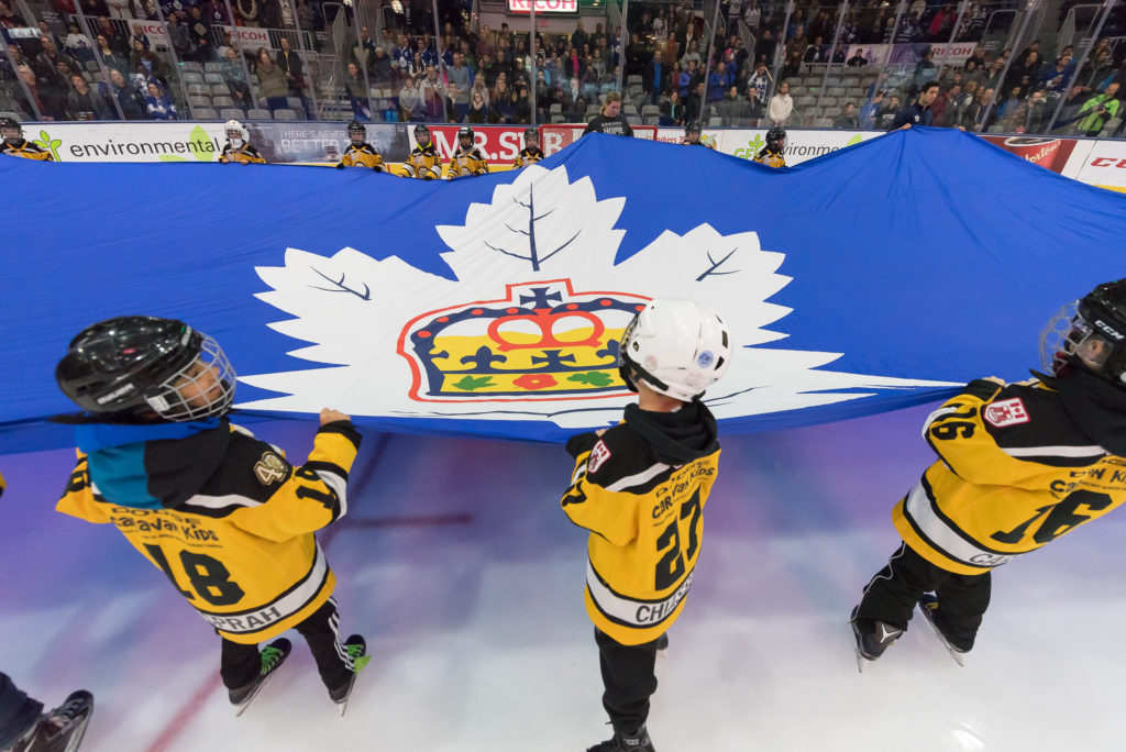 Minor hockey players hold a flag before puck drop