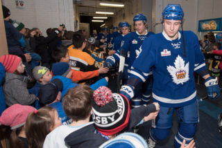 Minor hockey players give high-fives to the Marlies before a game.